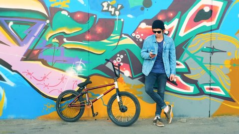 Young man with a cell phone is standing near a street wall and his BMX