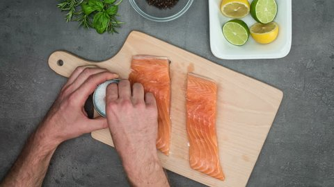 Man cuts small steak from salmon fish. Top view on food ingredients, stop motion animation. Shot B (see also shot A from SIDE).