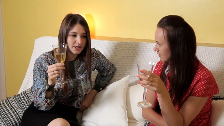 Beautiful Young Girls On A Rainy Day Sitting At Home On The Couch Drinking Wine