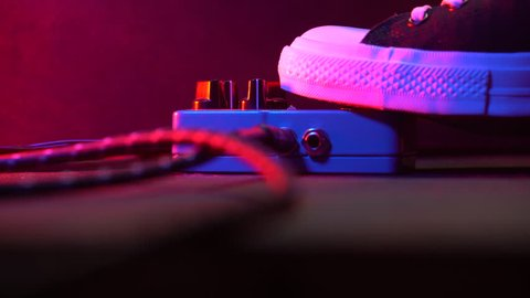 Foot in gumshoes pressing on loop pedal for electric guitar. Close up of guitarist step on effect machine on concert scene. Macro view. Neon light. 4k
