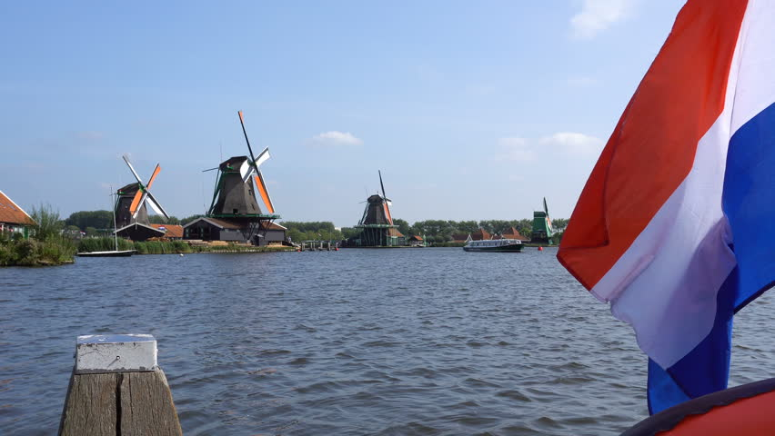 Traditional Holland Windmills and Floating Flag in Zaanse Schans, Netherlands. Touristic Village near the Amsterdam with the windmills and historical Dutch Houses