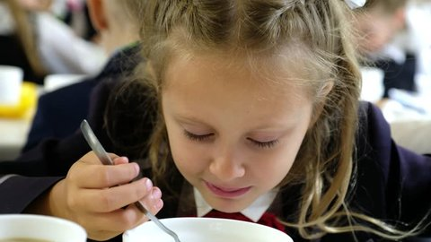 The girl at breakfast in the school canteen eating porridge plays with her spoon in the porridge and makes faces.