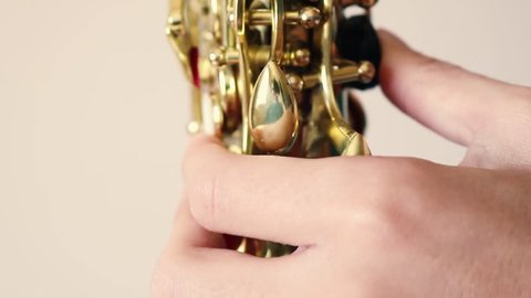 Details of a man playing a golden saxophone. A wind instrument seen very close to the camera.