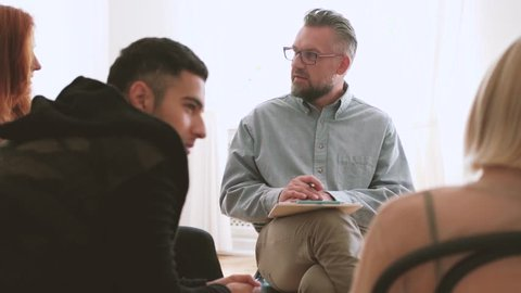 Professional psychotherapist talking with young rebellious people during meeting