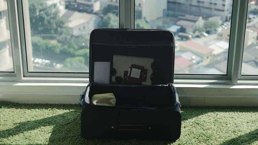 Travel preparations concept: travellers packing bagagge for summer vacation. Young family putting clothes in suitcase, preparing bag for trip together. #1016611090