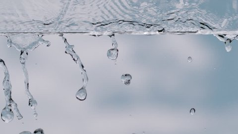 slow motion drops and water on a glass