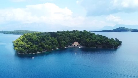 Aerial drone video of iconic uninhabited island of Madouri in bay of Nydri and Mansion of 19th-century poet Aristotelis Valaoritis, Lefkada island, Ionian, Greece