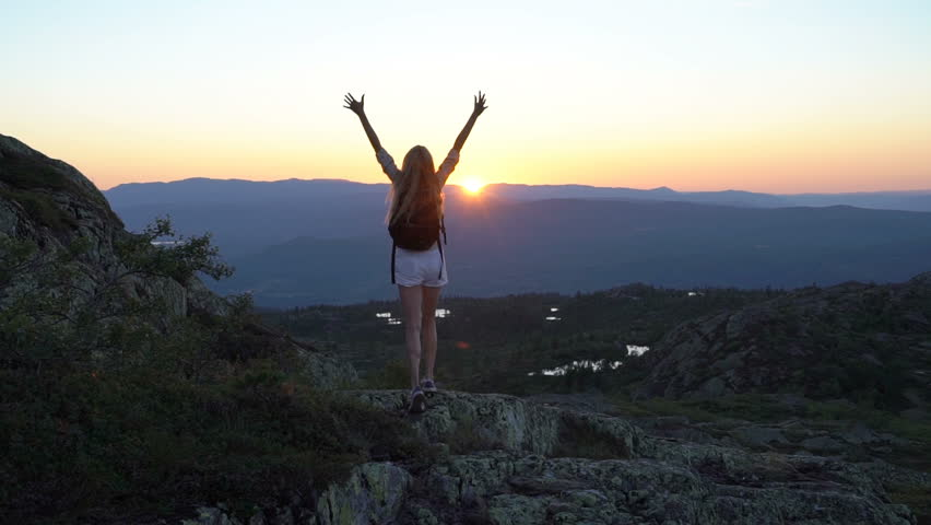 Happy young woman on the sunset high in the mountains with open waving hands. Slow motion #1016690830