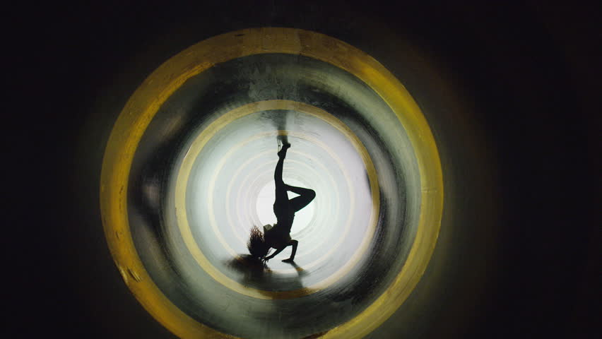A silhouette of beautiful sexy girl , woman dancing inside circle tube . Against colored & gray background . Real decoration . None computer graphics . Shot on Arri Alexa Cinema Camera in 4K .