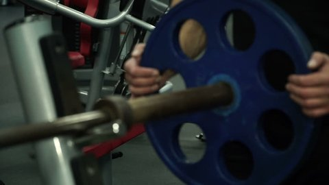 Close-up of multi-ethnic man puts metal disc on sports projectile for strength training.