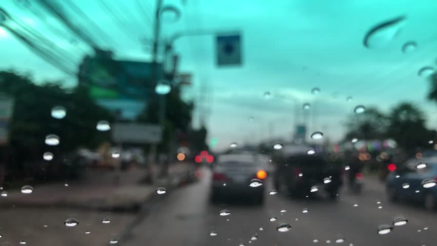 Motion movement with traffic in the city on a rainy day, Raindrops falling on car windshield. Blur background. Selective focus. | Shutterstock HD Video #1016746240