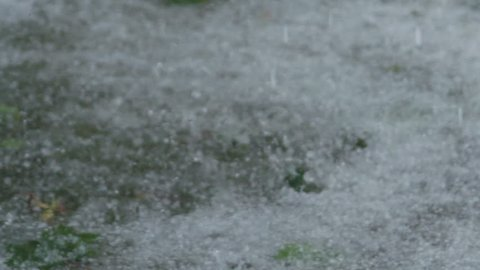 Slow motion closeup of hailstones falling on the pavement during strong hailstorm