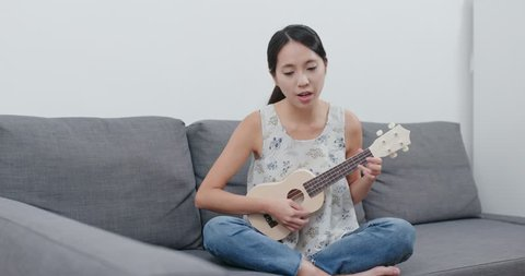 Woman singing with ukulele at home