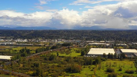Aerial drone footage industrial warehouse district auburn Washington by mountains
