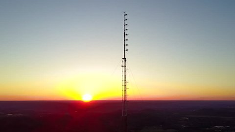 Aerial view of a tall broadcast tower ascension at sunset. Reversible for descent. FM antennas, microwave antennas, grid antennas, beacon lights, anti-lighting array, and multiple coax lines included.
