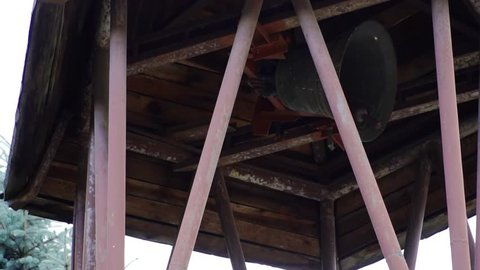 Antique rusty church bell ringing inside belfry in slow motion.