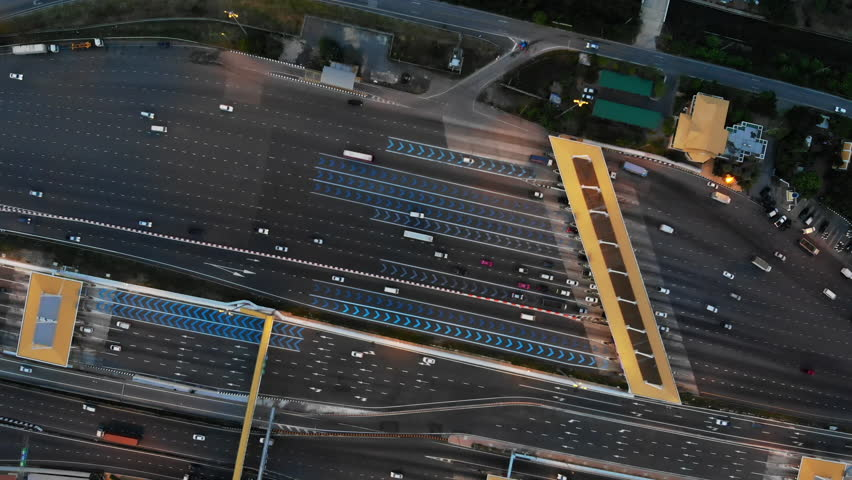 Aerial top down view over expressway toll gate with many vehicles passing through and pay fee.