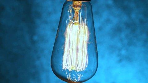 Vintage light bulb pulsating light in the darkness. Edison filament light bulb retro style.