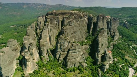 Aerial shot slowly moving historical place beautiful natural old mountain in Greece Meteora monasteries on peak located in amazing valley with hilly terrain covered by green plants near city Kalambaka