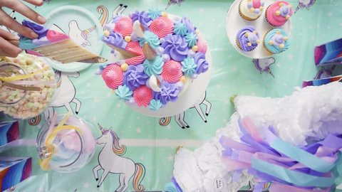Slow motion. Slicing unicorn cake at little girl birthday party.