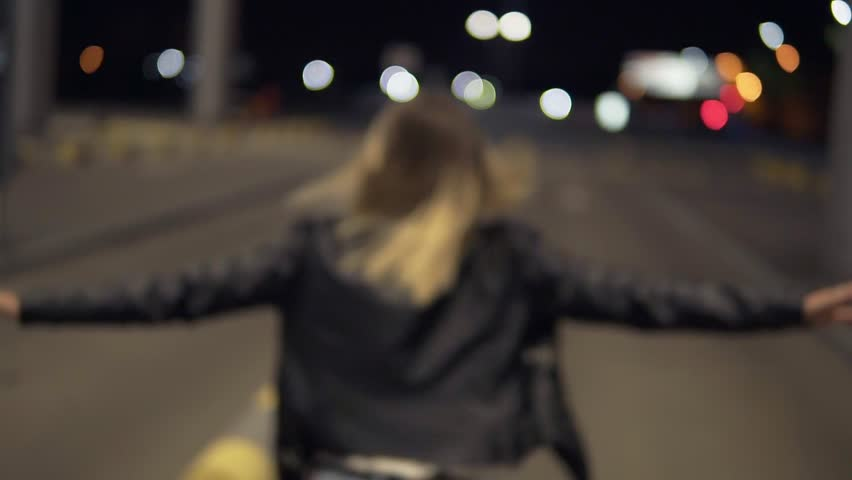 Happy blonde woman having fun outdoors at the nighttime. near the airport building. Running, immitating plane, jumping on bumpers. Wearing jeans and black jacket. Rare view