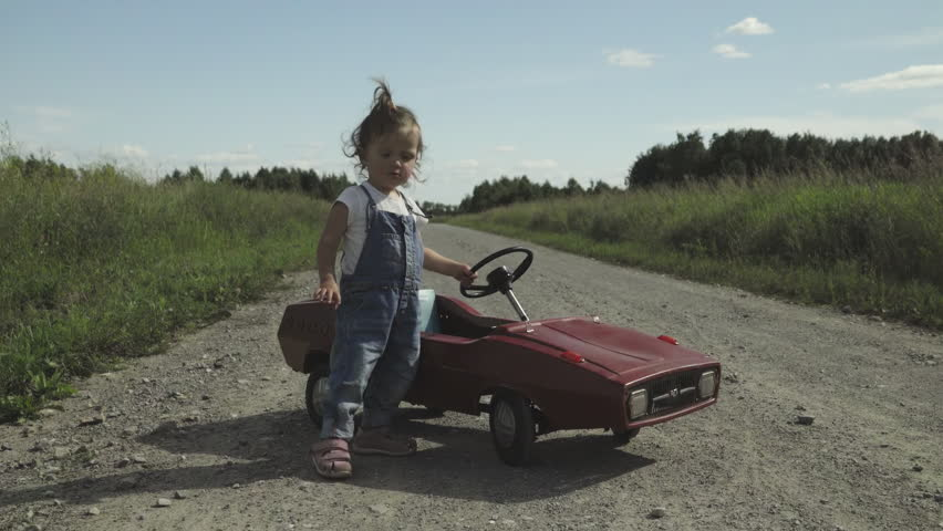 A little girl checks the wheels of a toy car and pushes her
