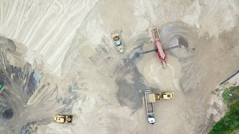 Excavator loader in sand quarry. View from above. Aerial view dumper trucks with cargo sand ridesing on territory sand factory. Tipper trucks on industrial area. Sand work