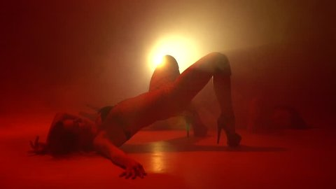 Two women in stockings are dancing a strip dance on the floor in the smoke, bit slow motion
