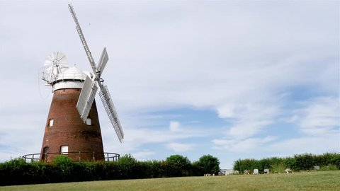 Traditional Old English Windmill. A quaint rustic scene with a traditional old English windmill set against a cloudy blue sky near the village of Thaxted, Essex.