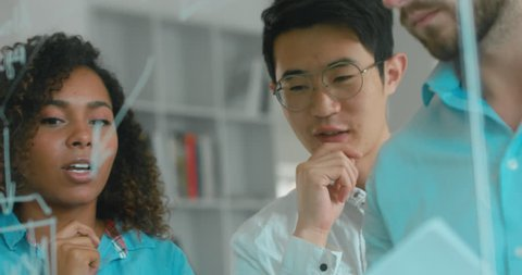 Multi racial team of employees drawing and discussing flowchart diagram in a modern office. 4K UHD 60 FPS SLOW MOTION