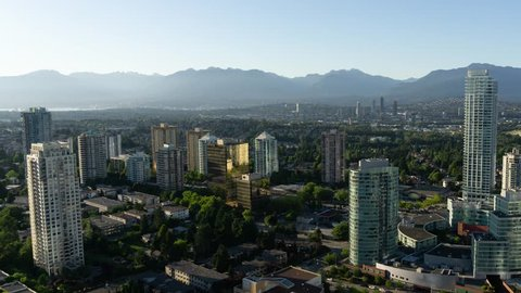 Aerial view of a modern city during a vibrant summer sunset. Taken near Metrotown, Burnaby, Greater Vancouver, BC, Canada.