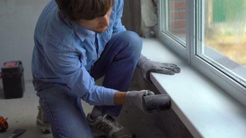 Young man installing windowsills of a plastic window