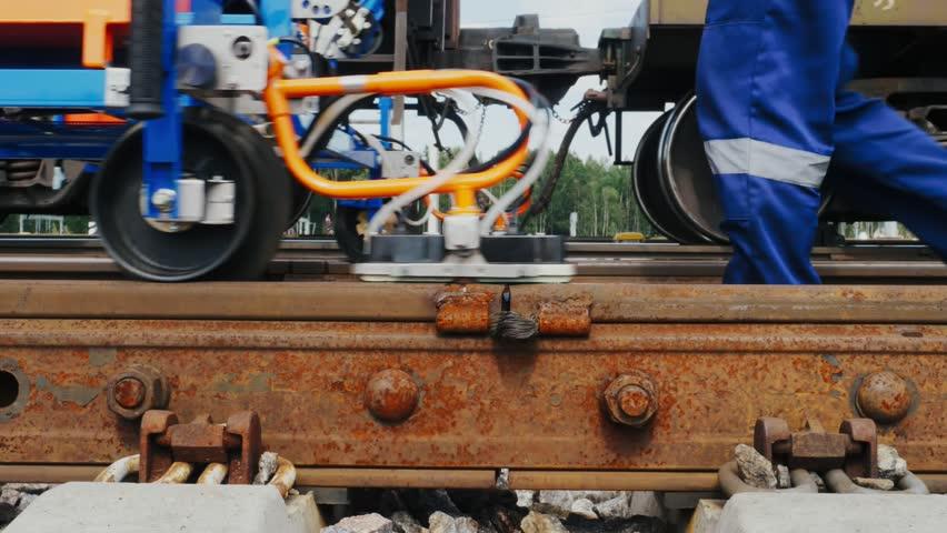 Railroad worker lubricates rails anti-corrosive liquid