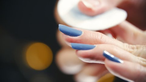 Removing blue color from fingernails close-up 4K. Long shot of person's long blue fingernails in focus with black background decorative lights out of focus.