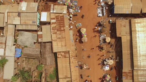 Gradual aerial nadir rise and reveal of a West African marketplace and the intersection of two busy dirt roads.