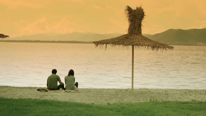 Man and Woman Sitting Along Summer Beach at Sunset . Young couple on lonely beach . Romantic couple is enjoying sunset . Silhouette of couple at the sea background . A pair of lovers watching the sky.