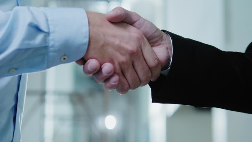 Two business partners shake their hands | Shutterstock HD Video #1016992750