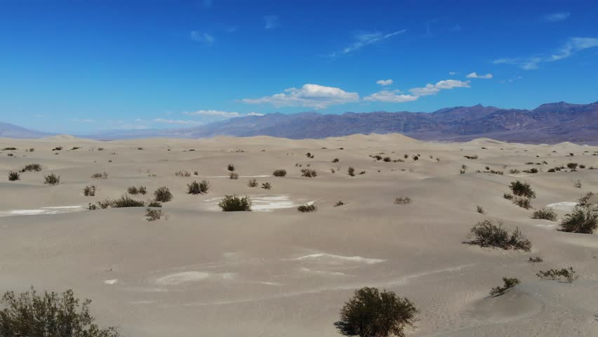 Drone Views Flying Away From Mojave Desert Rocks, Sand Dunes and Cactus Plants, Clear Blue Sky On Horizon With Rocky Mountains In Distance  | Shutterstock HD Video #1016994220