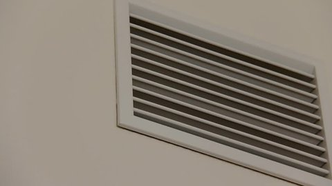 Plastic white ventilating grate on the beige painted wall