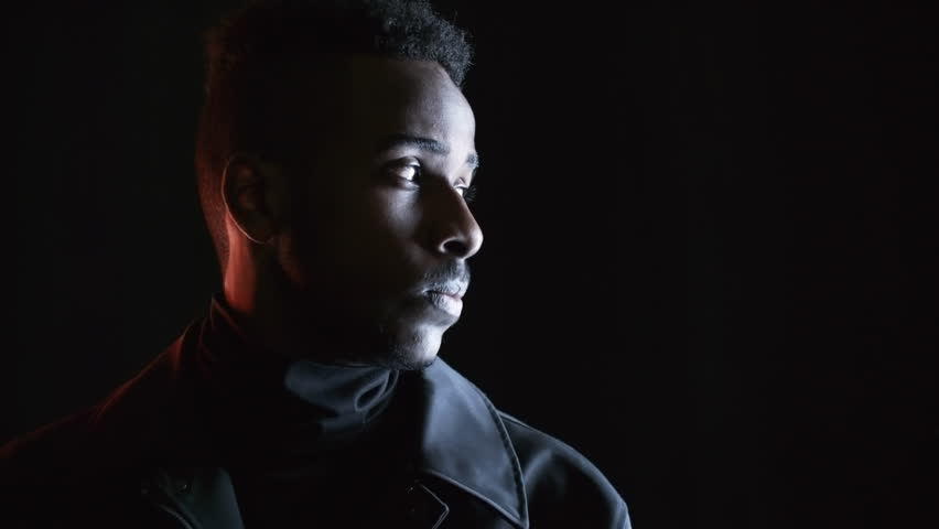 PAN low-key portrait with red lighting: serious black man in leather jacket standing isolated on dark background and looking away, then turning his head and looking at camera with calm expression | Shutterstock HD Video #1017001810
