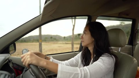 Asian woman with smart phone reading incoming message make worry when driving car