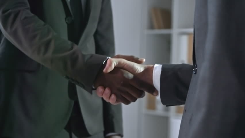 Medium shot of two unrecognizable multi ethnic people in business suits shaking hands when standing in office | Shutterstock HD Video #1017048670