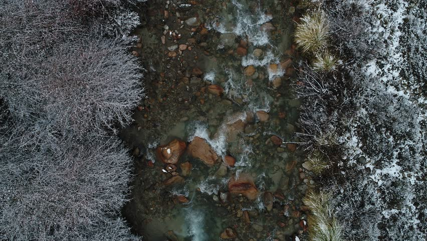 Aerial senital view of transparent water flowing along rocky Tunuyan river. Snowy vegetation at river bend. Winter cold day. Nature seasons. Valle de Uco, Mendoza, Argentina.