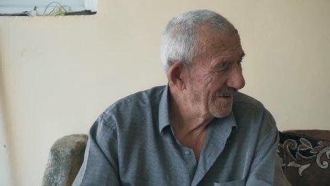 Positive elderly man talking. Closeup shot