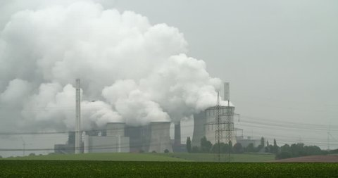 RWE power plant working on lignite producing electricity and huge gray  clouds of steam in Neurath, Germany, 4K