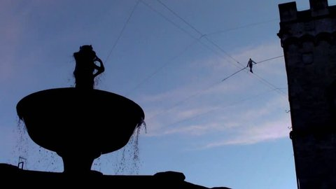 PERUGIA, UMBRIA, ITALY - DECEMBER 9, 2017: Funambulist Andrea Loreni crossing Piazza IV Novembre on a tightrope at a 40 metres heigth: Almost at the finish line (silhouette of the Fontana Maggiore)