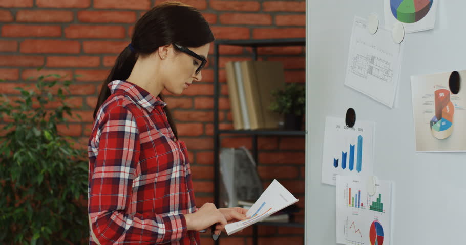 Caucasian young woman in the motley shirt and glasses pinning up some graphic and chart to the board in her office. | Shutterstock HD Video #1017151060