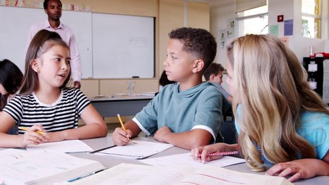 Male elementary school teacher comes to kids\xEA desk to help