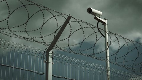 Concrete fence, barbed wire and surveillance camera