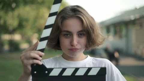 Serious young woman with short thick hair looking at camera. She is using clapperboard and starts laughing after that. Concept of filmmaking and acting. Slider slow motion portrait shot